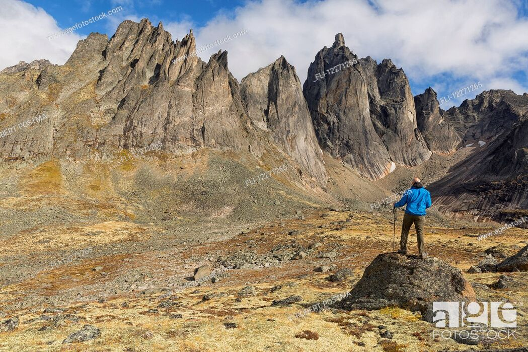 Imagen: Man standing on a rock overlooking the jagged granite peaks of Tombstone Territorial Park; Yukon, Canada.