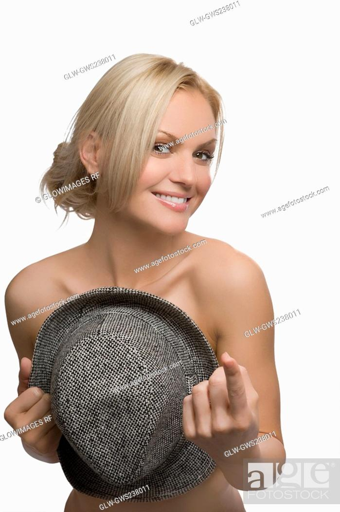 Stock Photo: Portrait of a young woman covering her breast with a hat and smiling.