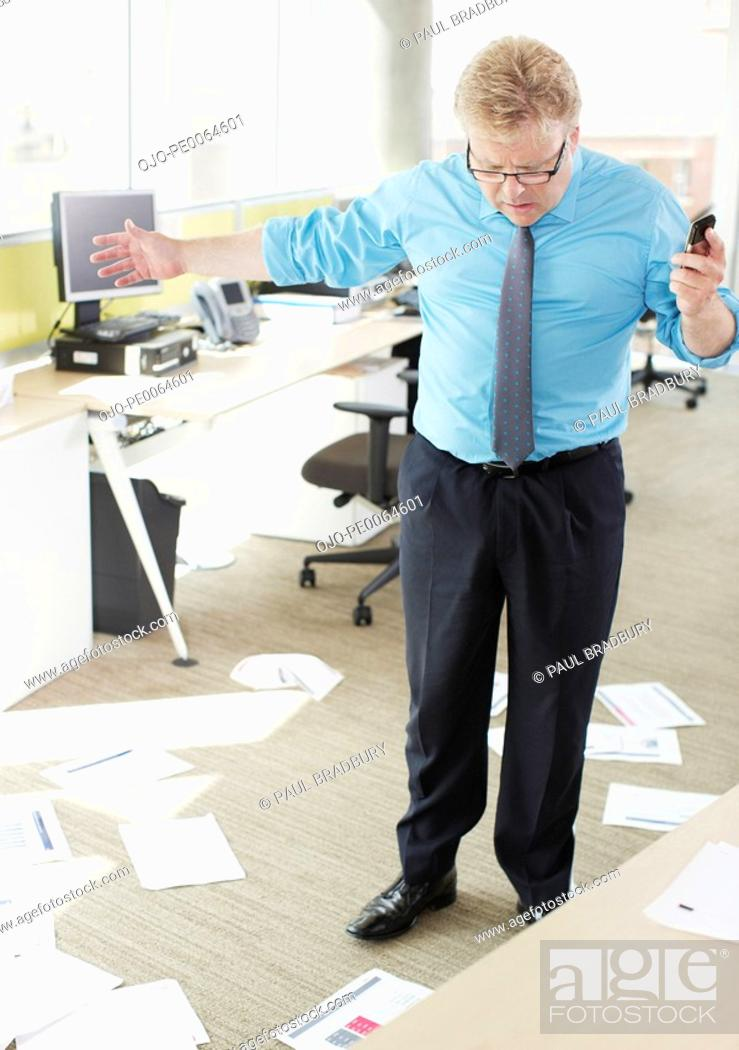 Stock Photo: Businessman looking at papers on floor.