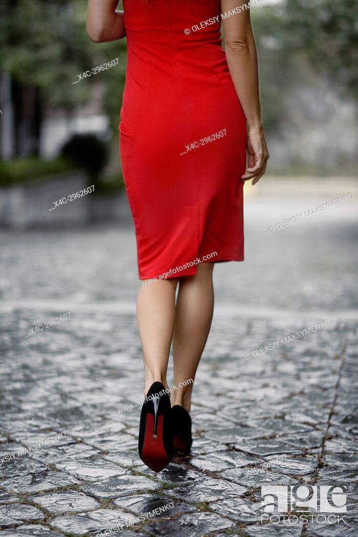 Stock Photo: Sexy woman in an elegant red dress walking away on a wet cobbled city street closeup of legs in high heel shoes.