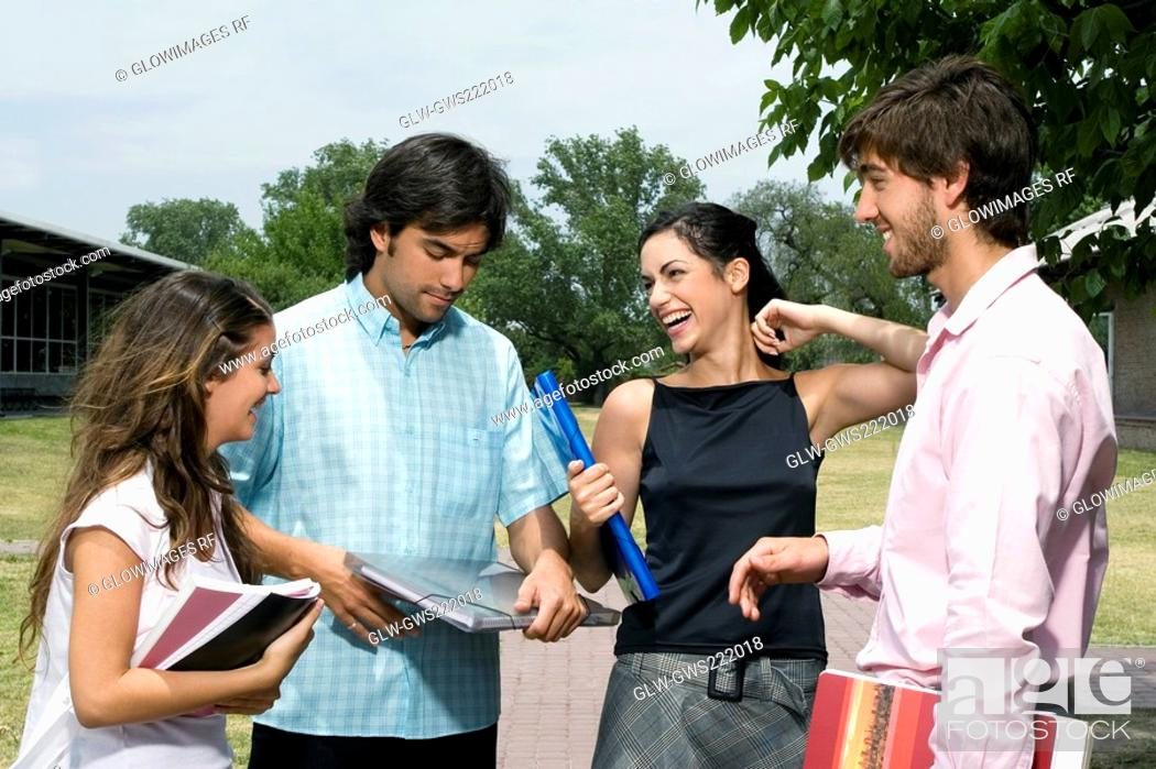 Stock Photo: Four university students standing on a footpath and smiling.