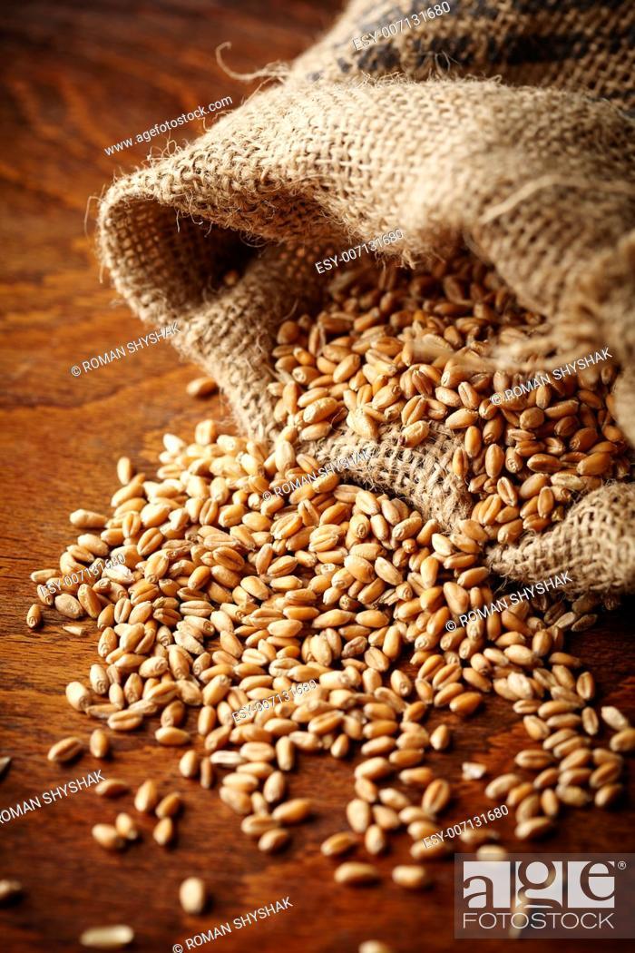 Stock Photo: wheat grain on wooden table.