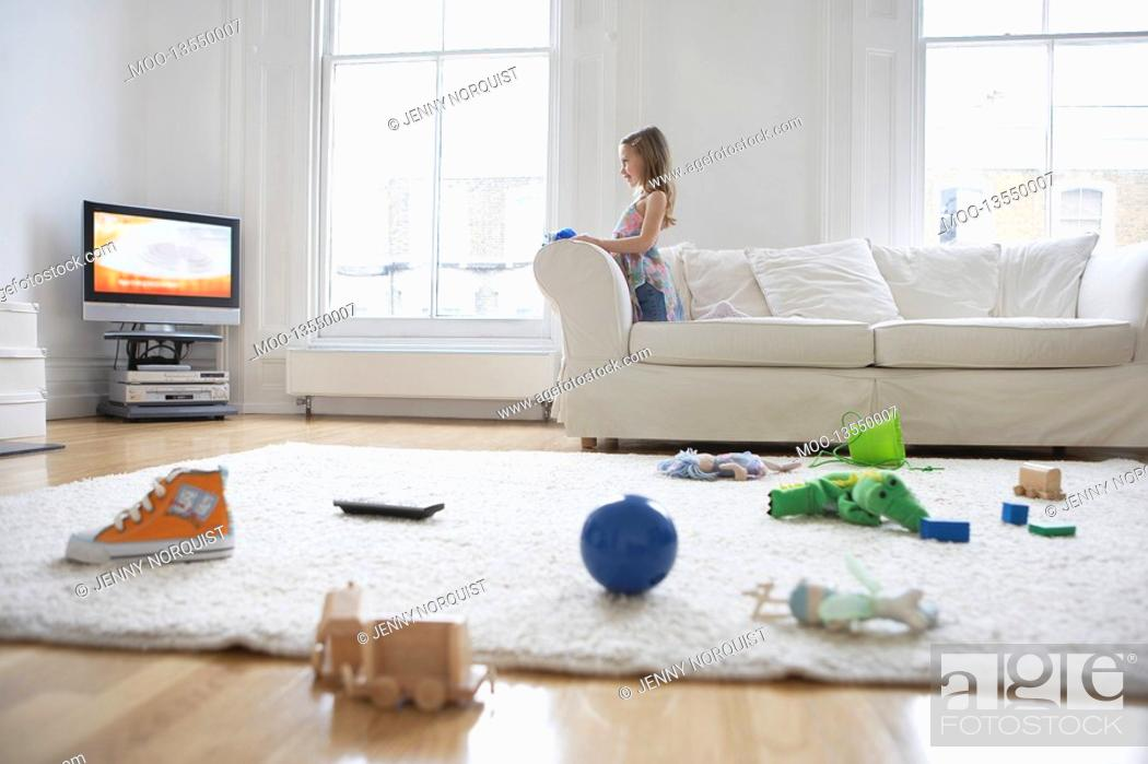 Stock Photo: Girl 5-6 watching television toys on floor in foreground.