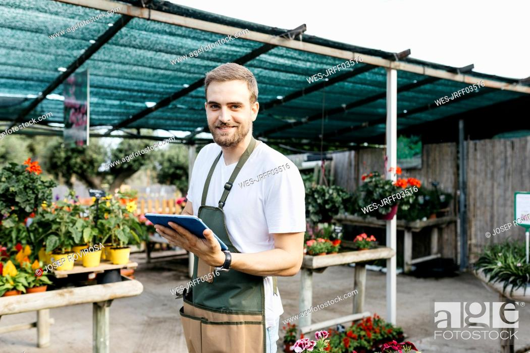 Stock Photo: Portrait of a smiling worker in a garden center using a tablet.