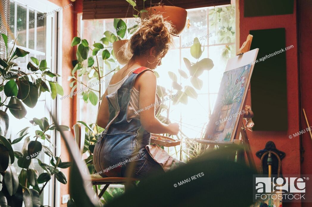 Stock Photo: Indoor shot of professional female artist painting on canvas in studio with plants.