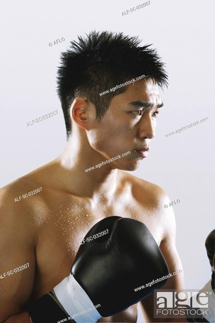 Stock Photo: Japanese boxer wearing gloves and sweating.
