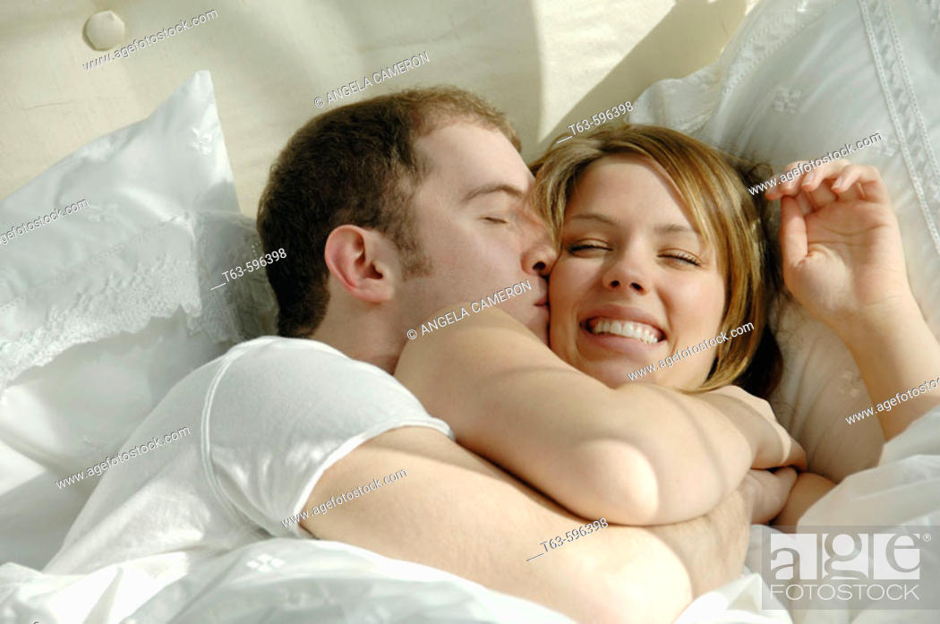 Stock Photo: Young couple in bed cuddling and playing together.