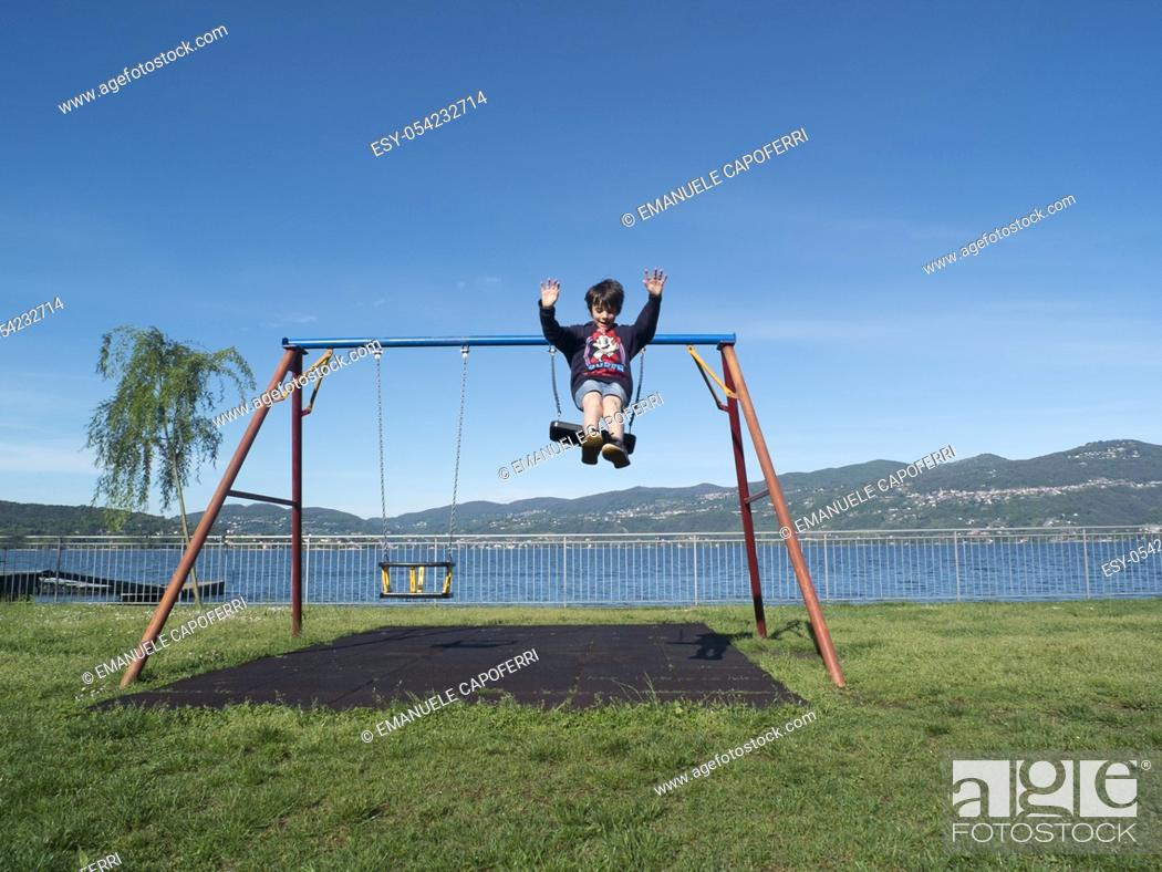 Stock Photo: Children play at the playground with swings, Ispra, Varese, Lombardy, Italy.