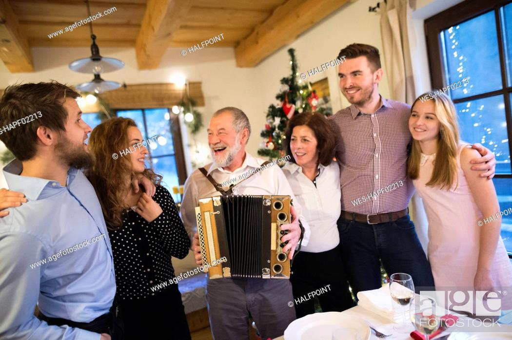 Imagen: Senior man playing accordion for happy family at Christmas.