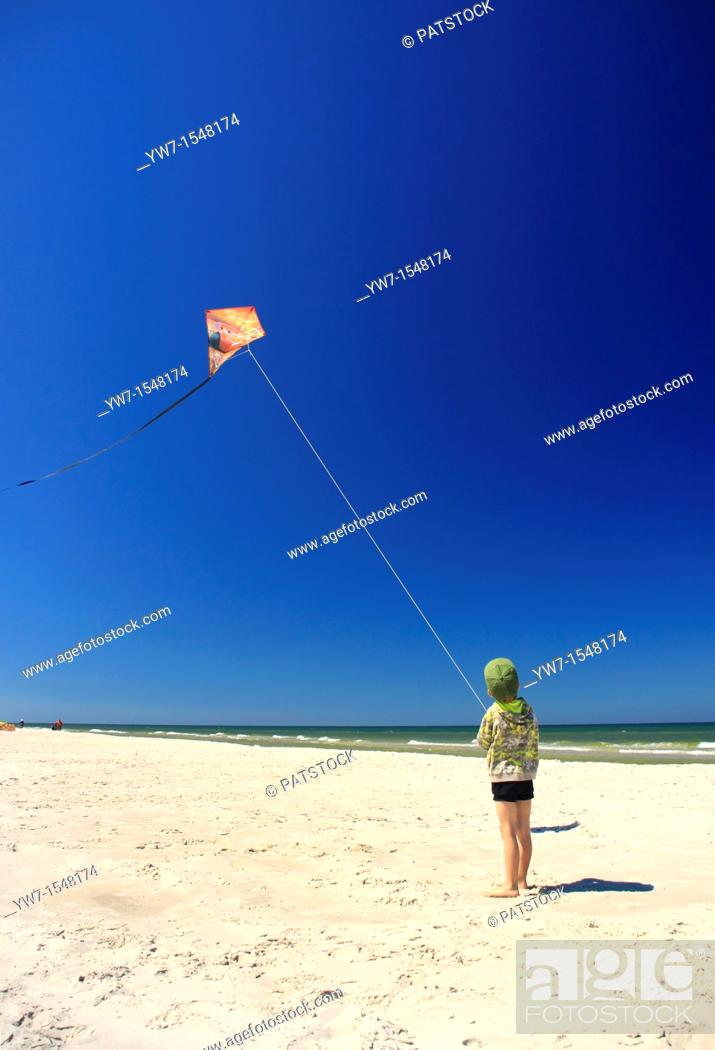 Stock Photo: 5 year old boy flying his kite on a beach.