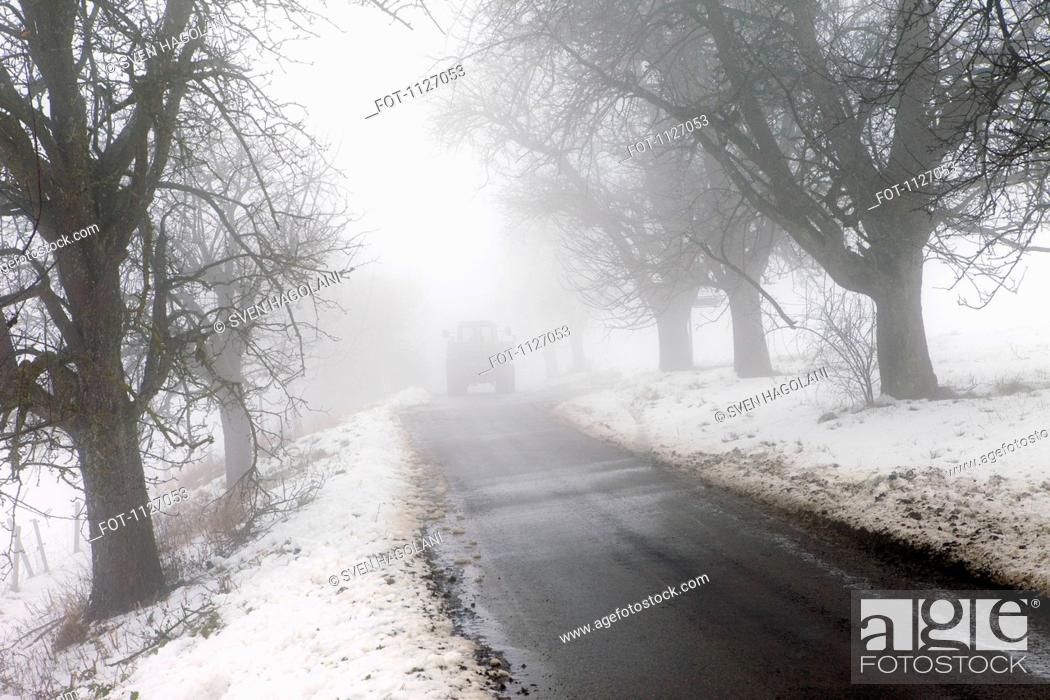 Stock Photo: On Winter road with tractor in distance.