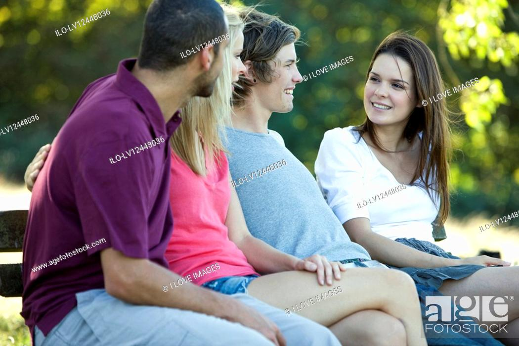 Stock Photo: Four people sitting on a bench, talking.