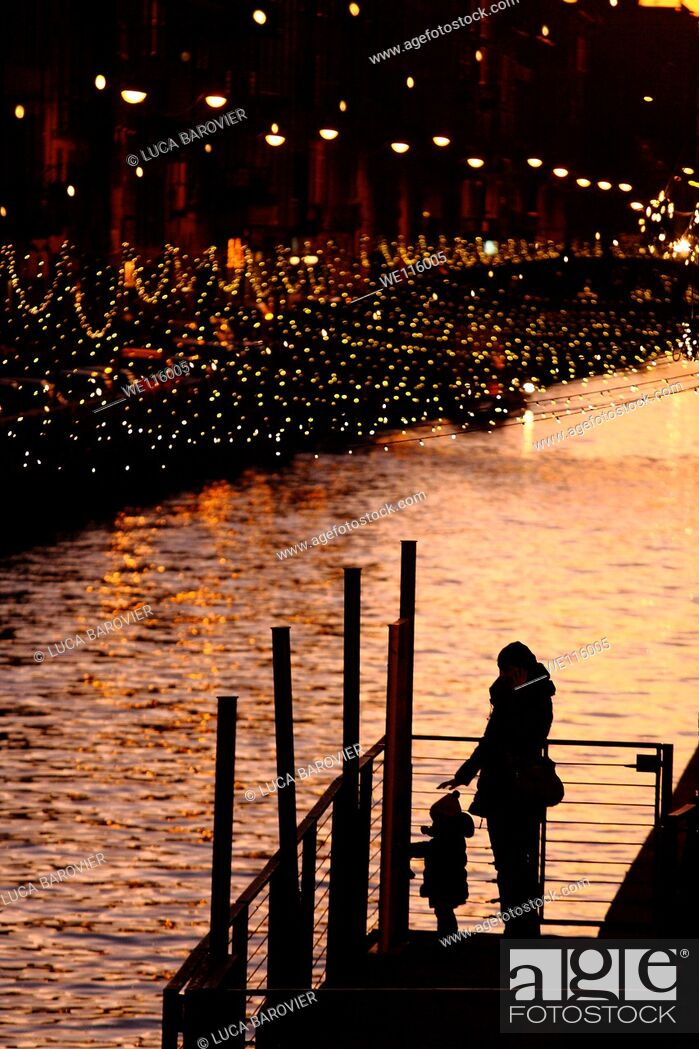 Stock Photo: Mother and son silhouette on the Naviglio Grande, Milan Italy.