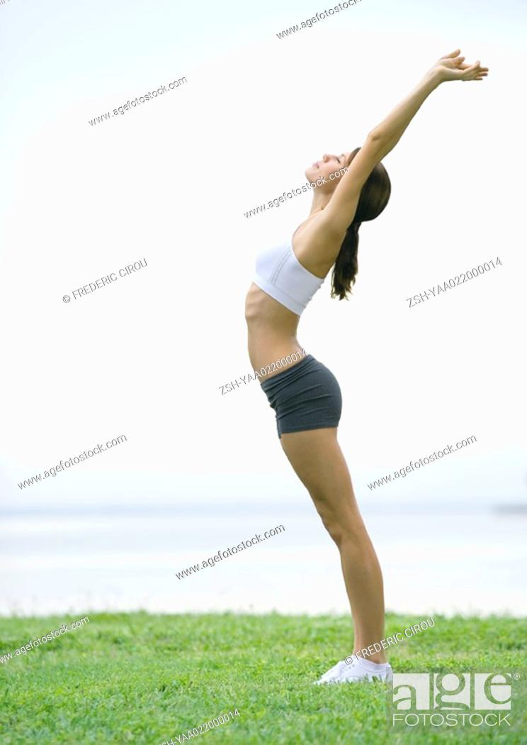 Stock Photo: Young woman stretching, side view, outdoors.