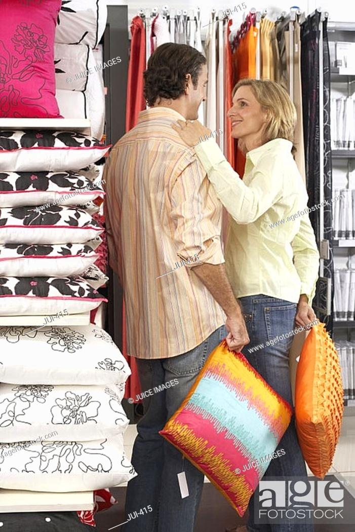 Stock Photo: Couple shopping for cushions in department store, woman placing hand on man's shoulder, smiling.