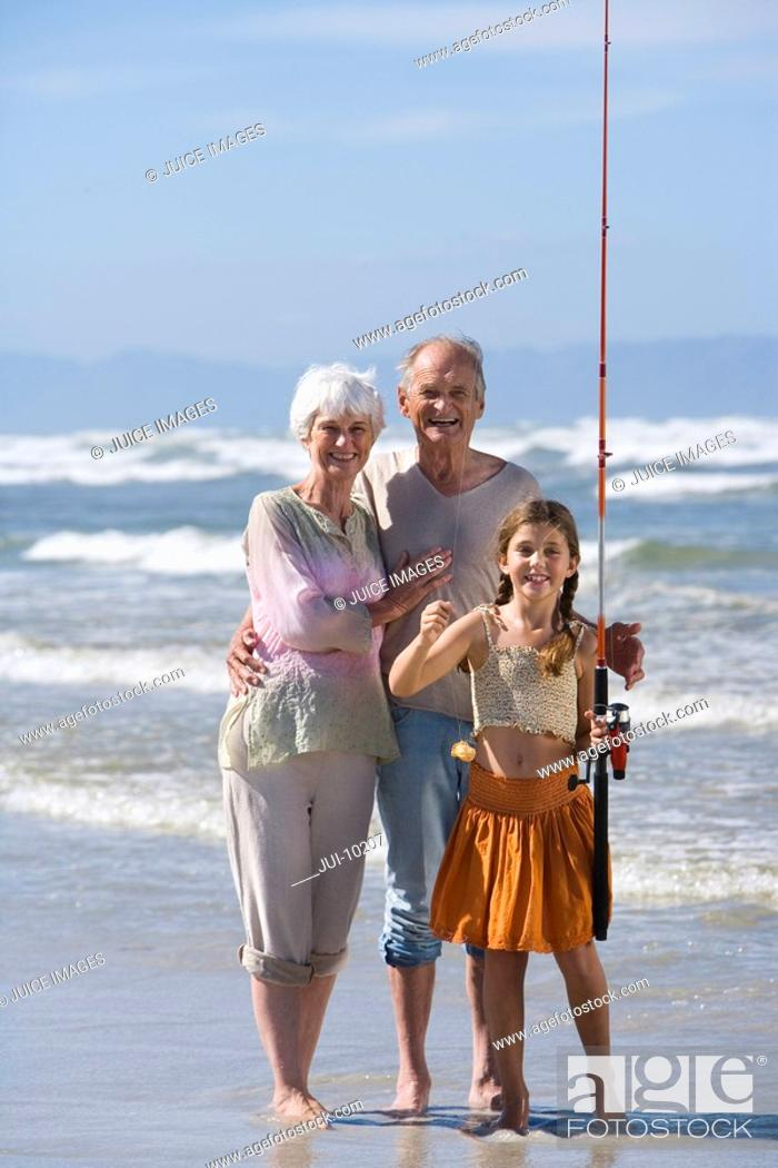 Stock Photo: Grandparents and granddaughter 7-9 with fishing rod on beach, smiling, portrait.