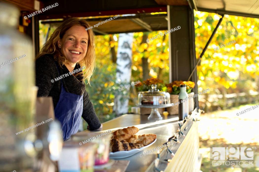 Photo de stock: Portrait happy female food cart owner working in park.