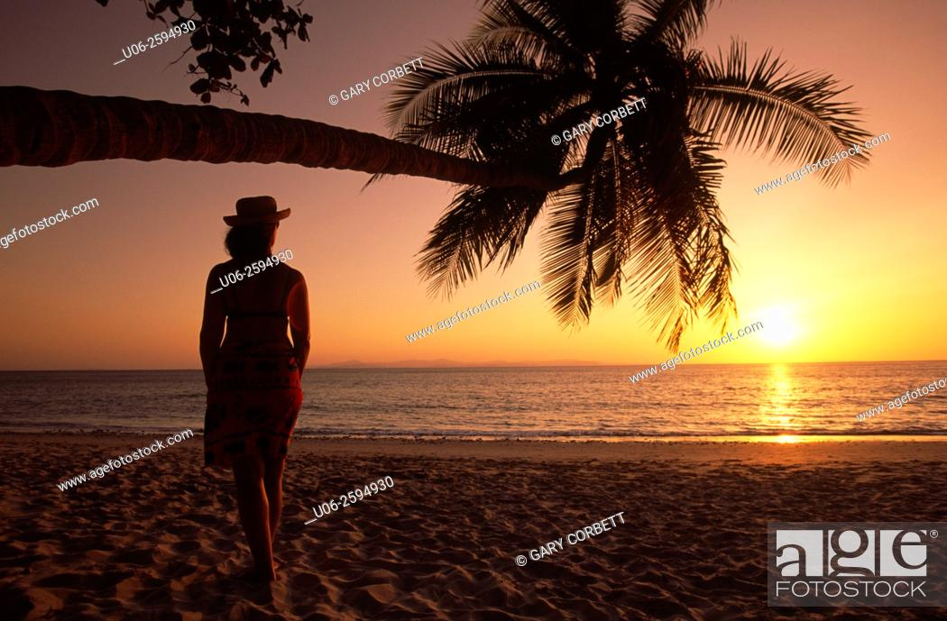Stock Photo: A woman looking at the sunset over the Pacific Ocean at a beach in Costa Rica.