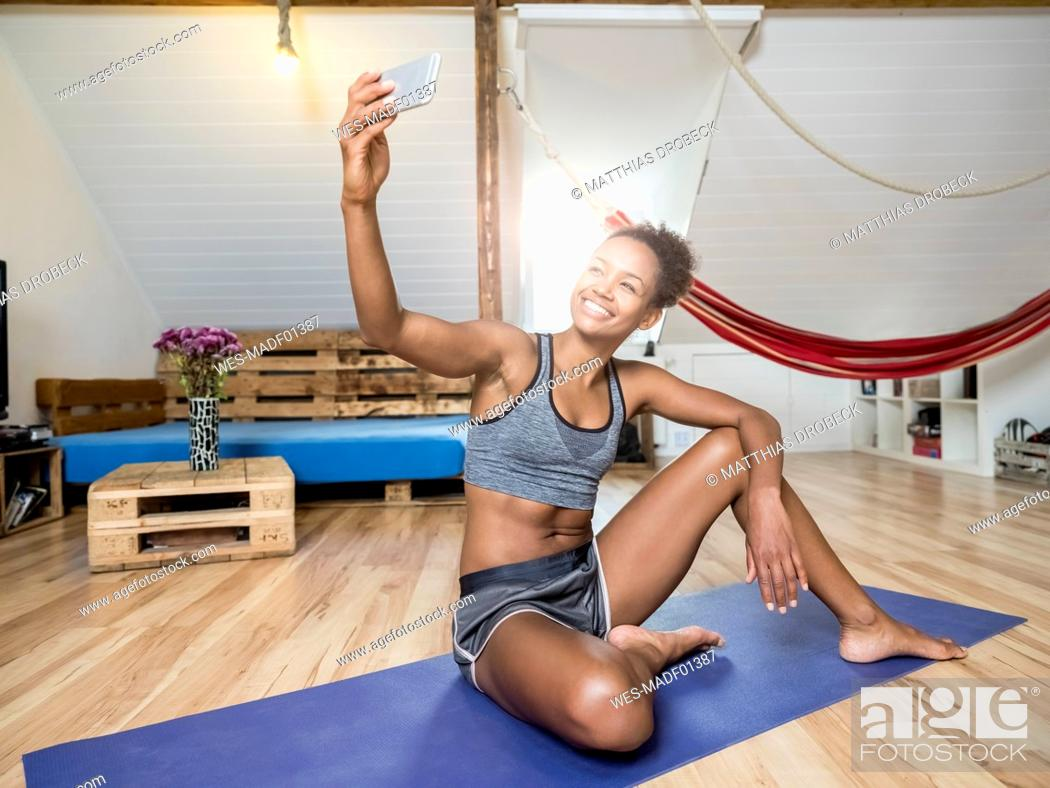 Stock Photo: Smiling young woman sitting on yoga mat taking a selfie.