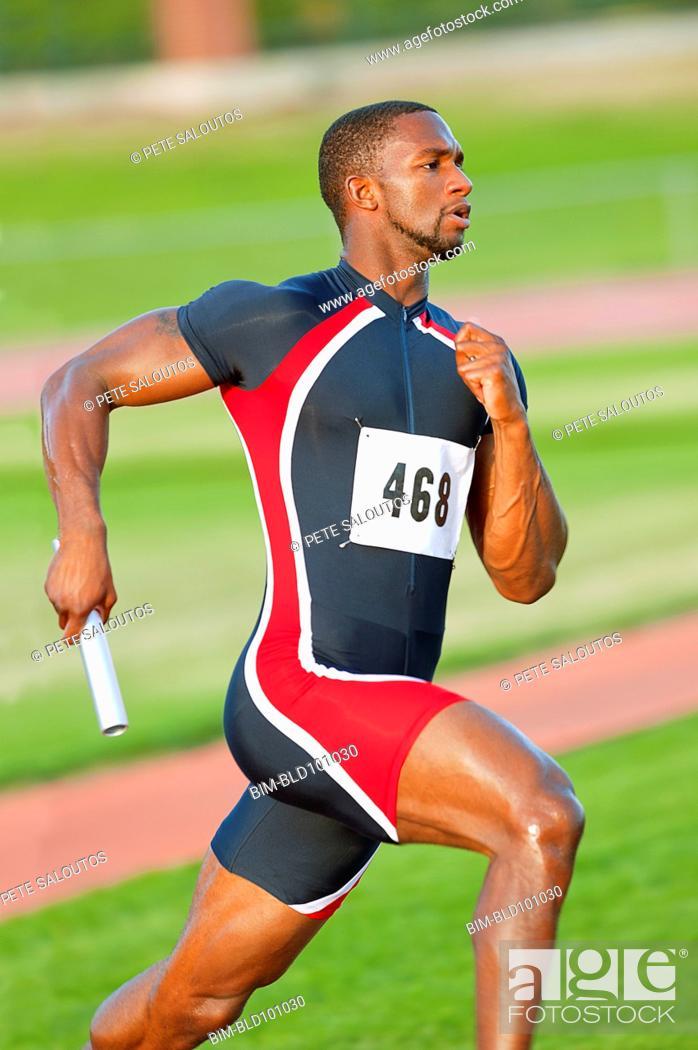 Stock Photo: Black runner carrying baton in relay race.