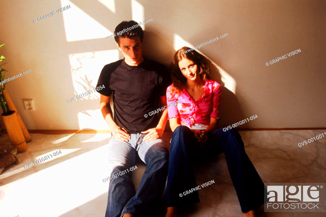 Stock Photo: Portrait of young couple sitting on the floor.
