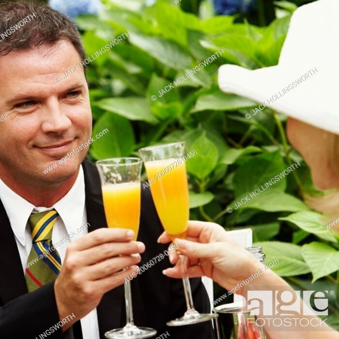 Stock Photo: Close-up of a couple toasting glasses of juice.
