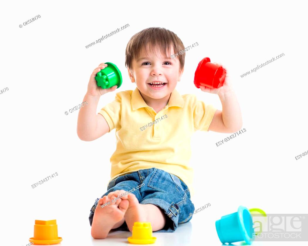 Imagen: smiling child boy playing with color toys isolated on white.
