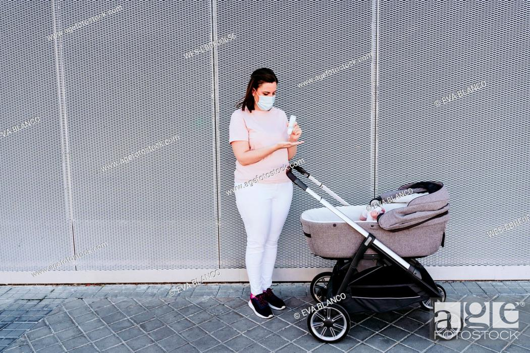 Imagen: Mother wearing protective mask, using hand sanitizer, baby girl in stroller.