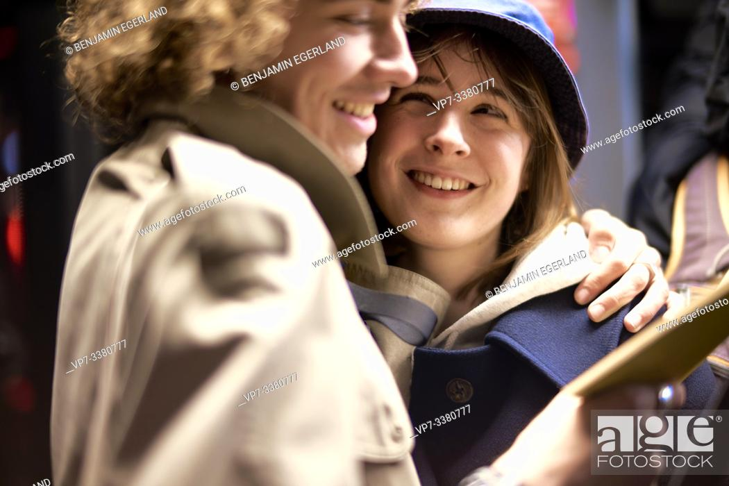 Stock Photo: Couple looking at book. Nightlife, in Berlin, Germany.