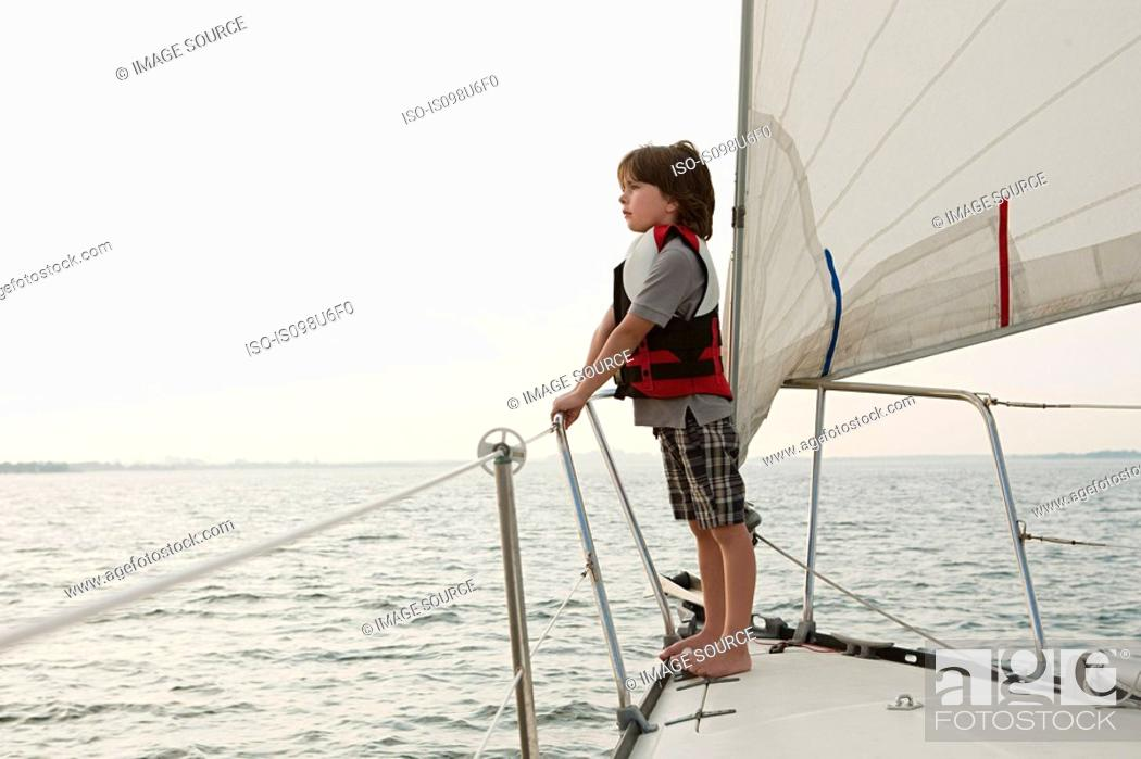 Stock Photo: Young boy on board yacht, looking at view.