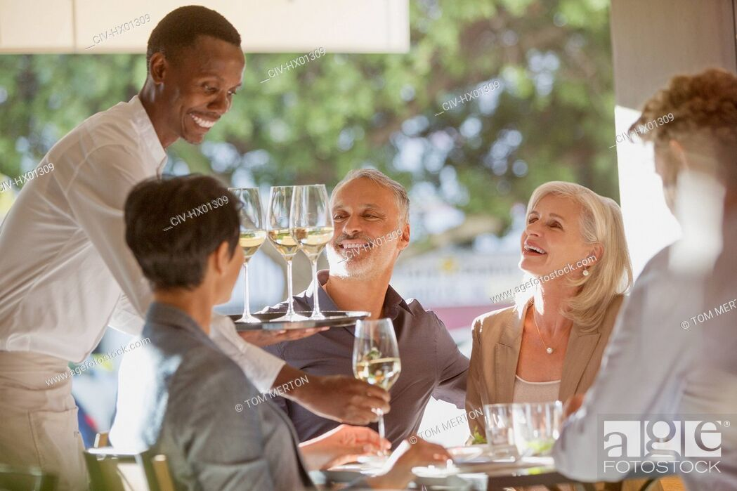 Stock Photo: Waiter serving white wine to couples at restaurant table.