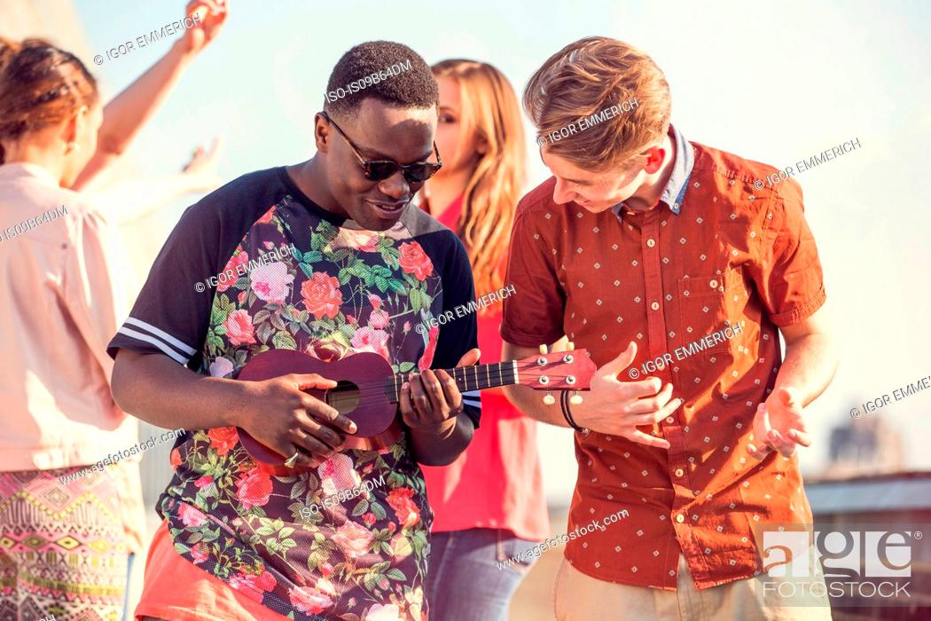 Stock Photo: Young man playing ukulele at roof party in London, UK.