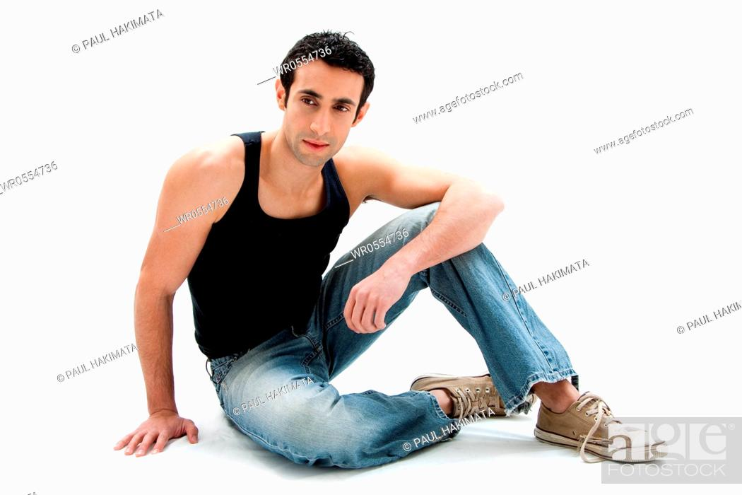 Imagen: Handsome Caucasian guy wearing black tank top and jeans sitting on floor, isolated.