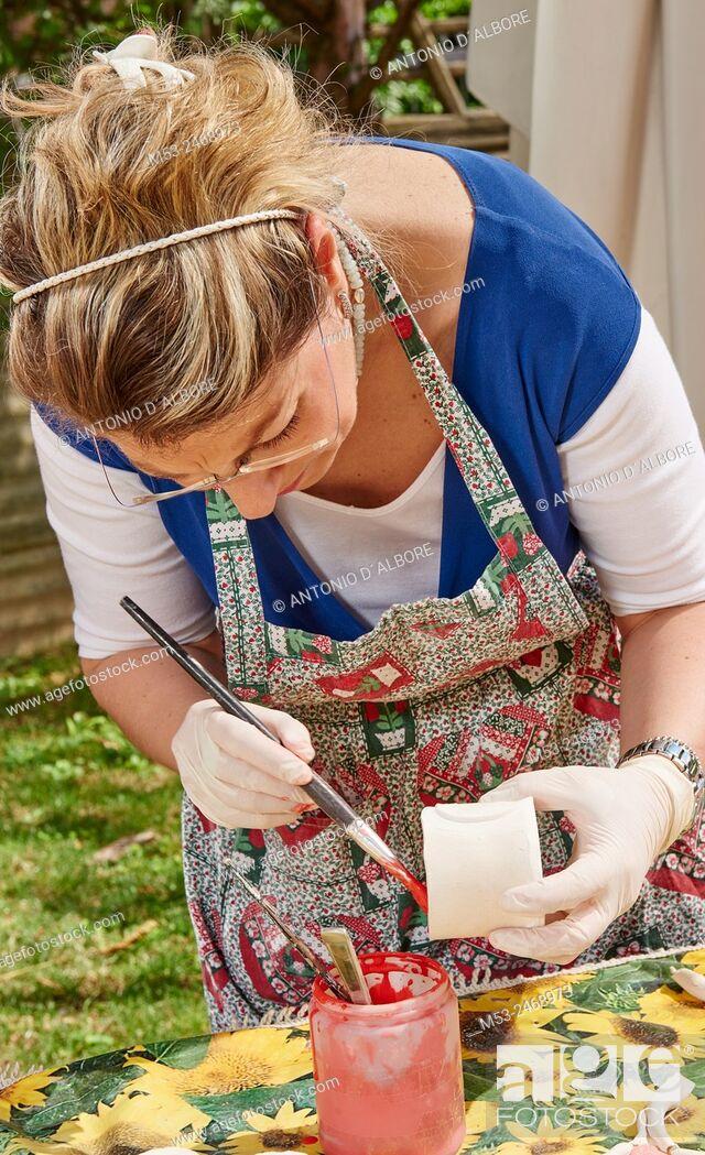 Imagen: An amateur artist apply raku glaze on ceramic object.