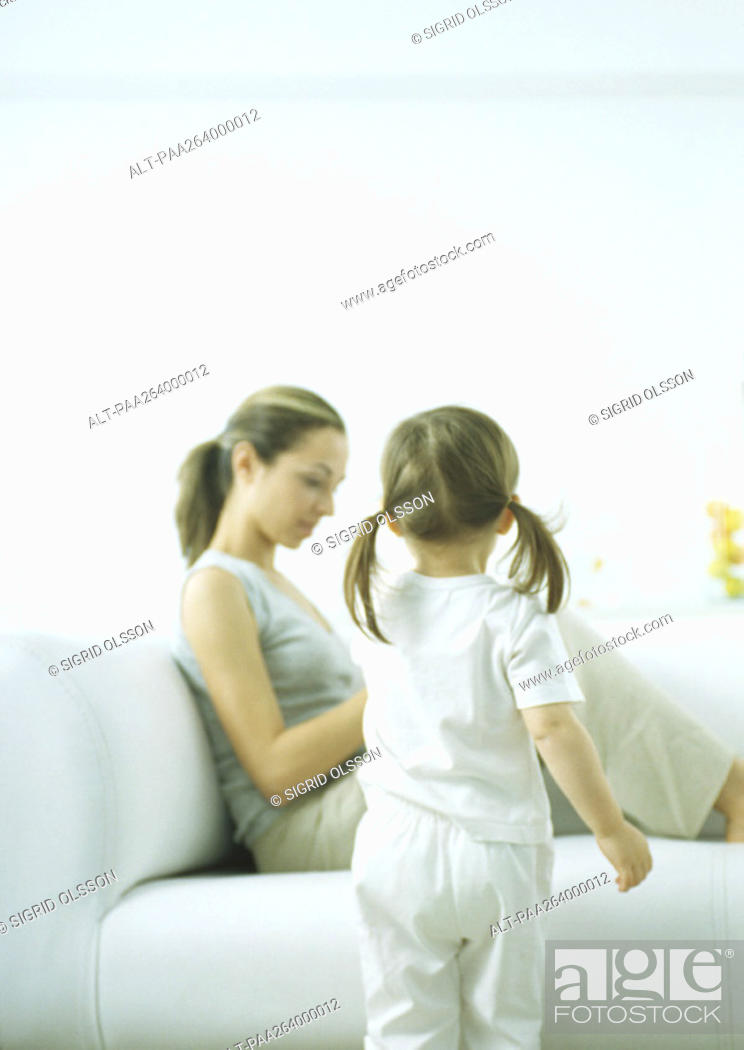 Stock Photo: Little girl with pigtails, rear view, and young woman sitting on sofa.