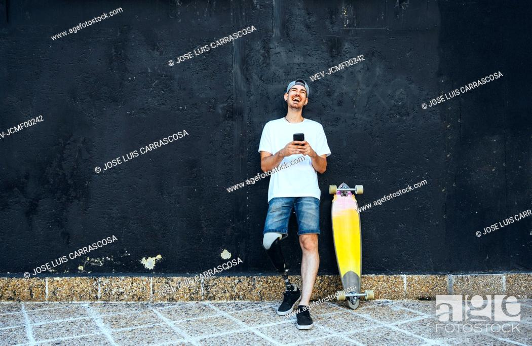 Stock Photo: Laughing young man with leg prosthesis and skateboard using smartphone.