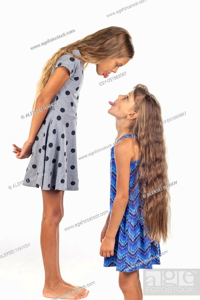 Stock Photo: A girl stands on a chair, another girl stands nearby, show each other tongues.
