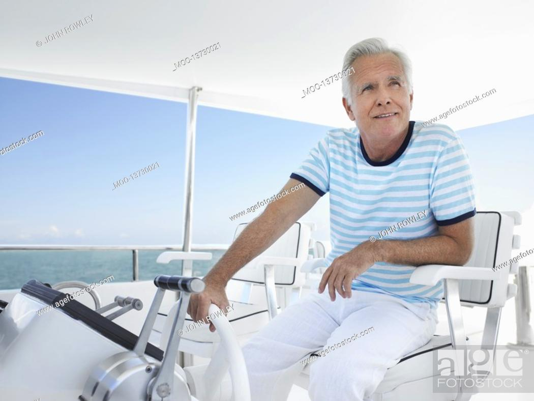 Stock Photo: Middle-aged man sitting at helm of yacht.