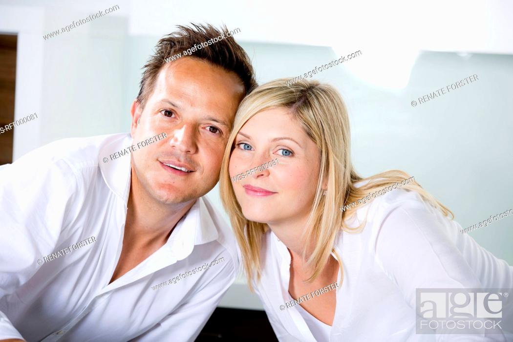 Stock Photo: Germany, Mid adult couple standing in kitchen very close, portrait.