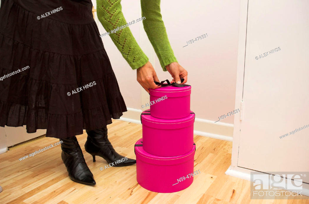 Stock Photo: Stack of three pink gift boxes on a wooden floor.