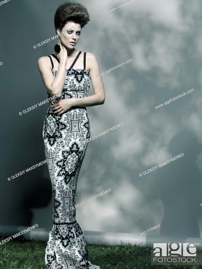 Stock Photo: High fashion photo of a beautiful woman wearing elegant long dress.