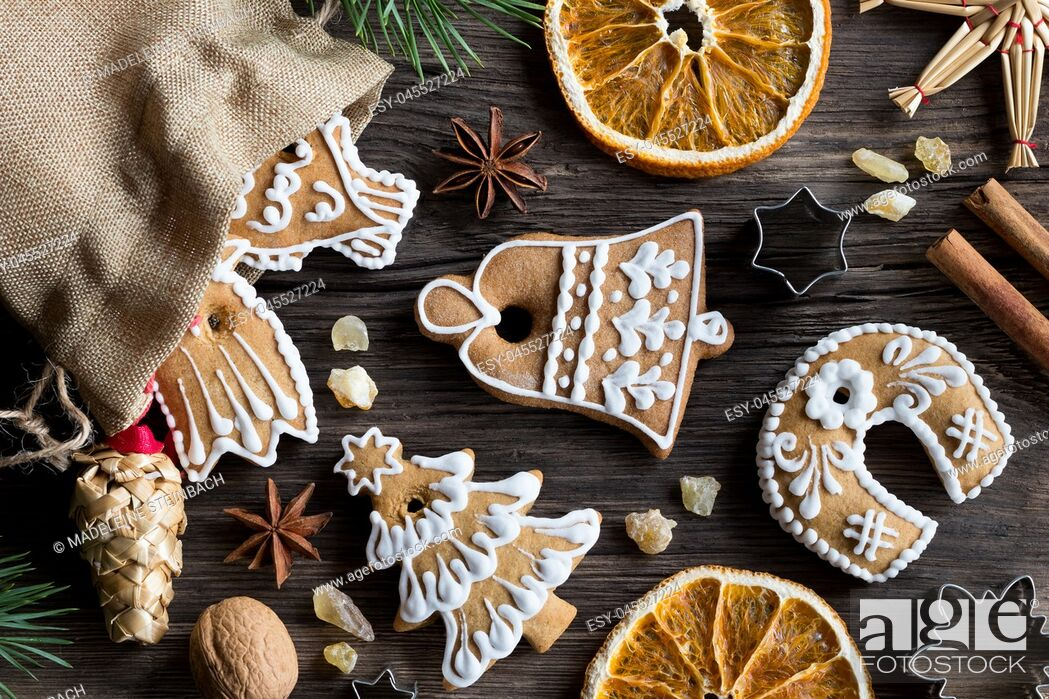 Stock Photo: Christmas decoration - a linen bag with decorated gingerbread cookies, straw ornaments, star anise, walnuts, cinnamon, frankincense resin and dried orange.