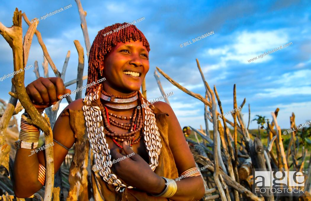 Stock Photo: Turmi Ethiopia Africa Lower Omo Valley village with Bena Tribe First Wife smiling in sunset in wood hut village 24.
