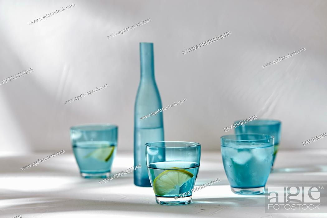 Stock Photo: glasses with water and lemons on white background.