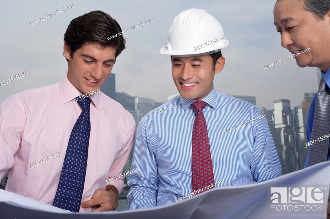 Stock Photo: Business men and construction site manager reading blueprints.