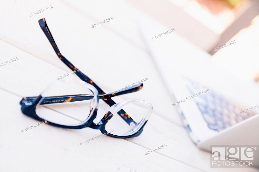 Stock Photo: Spectacles and laptop on porch table.