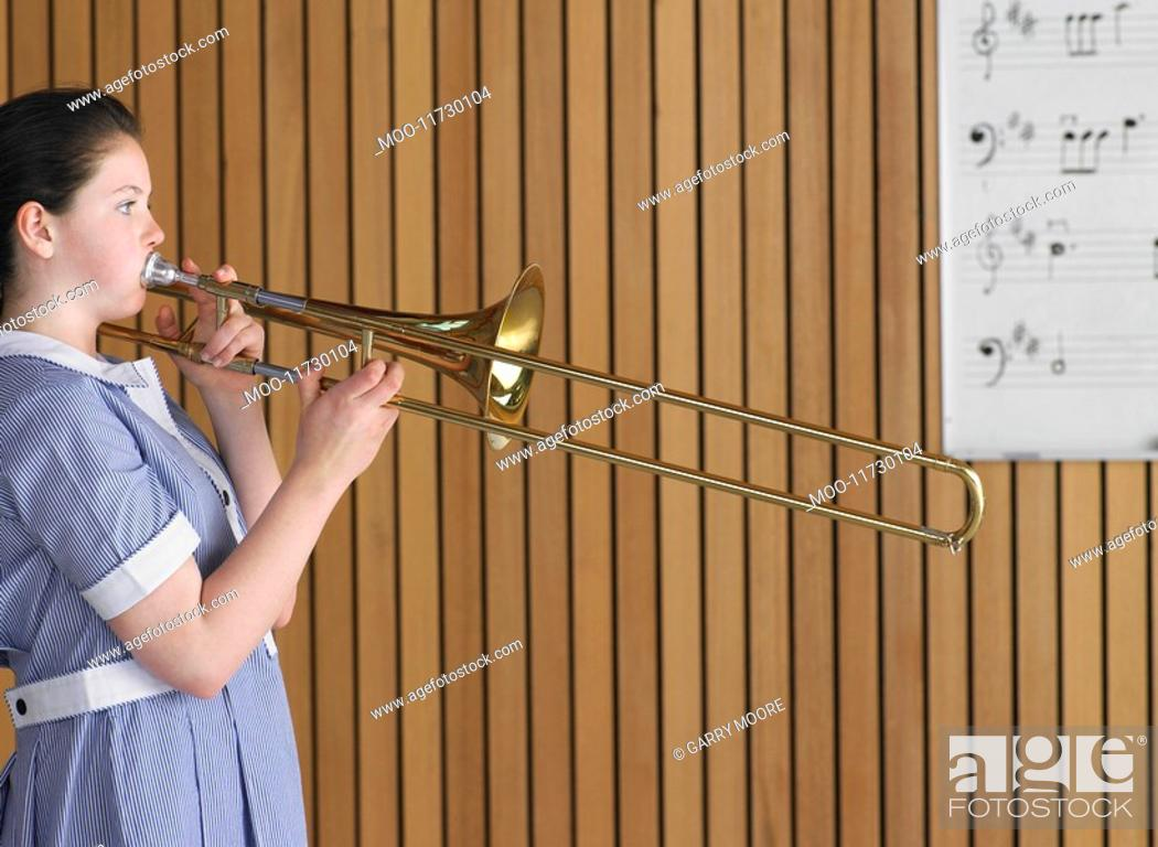 Stock Photo: High school girl playing trombone in class side view.