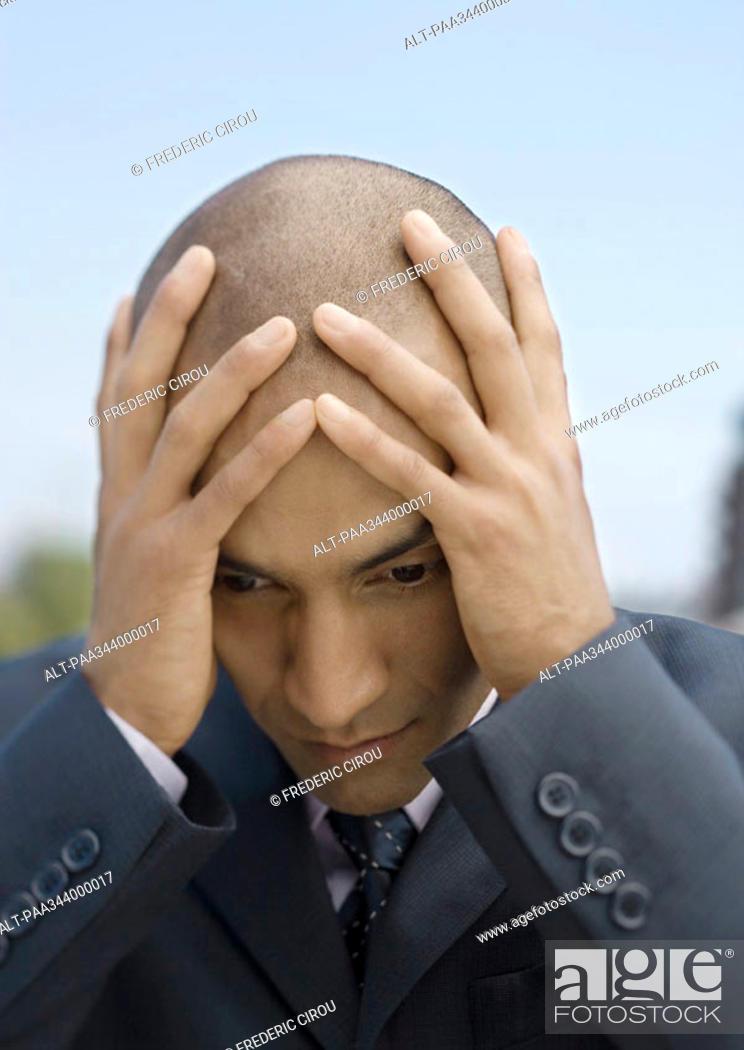 Stock Photo: Businessman holding head.