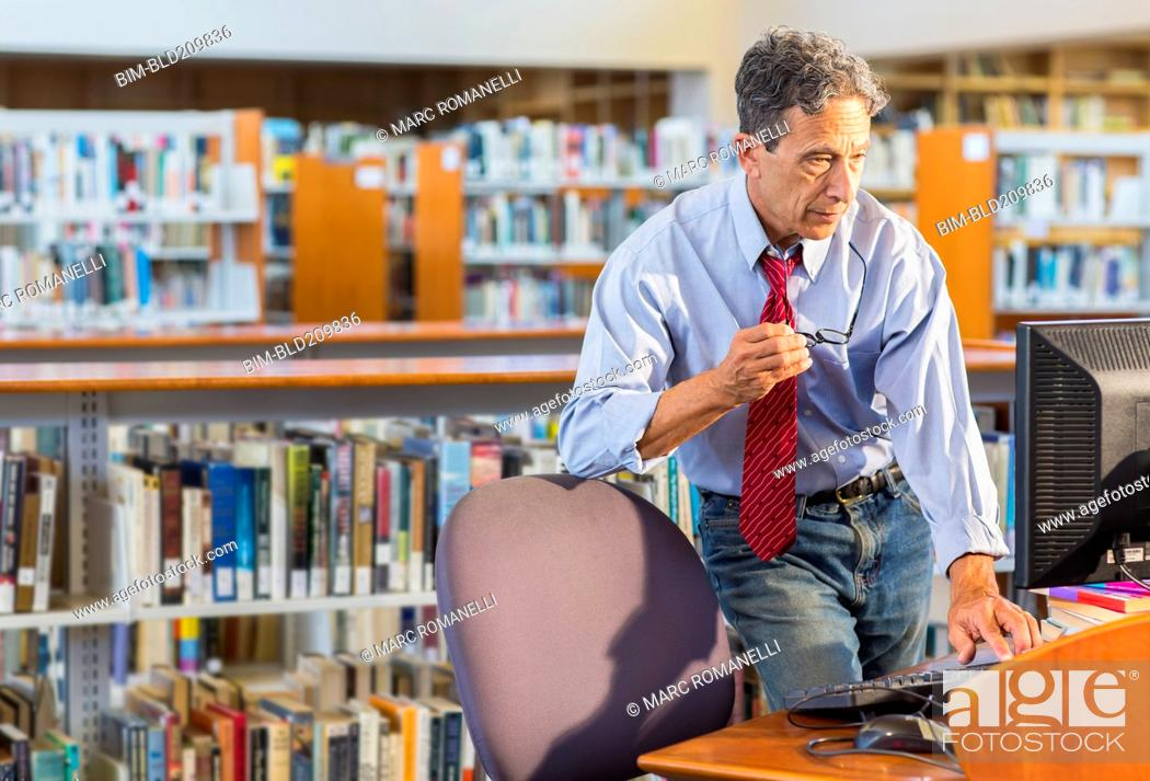 Stock Photo: Senior man working at computer in library.