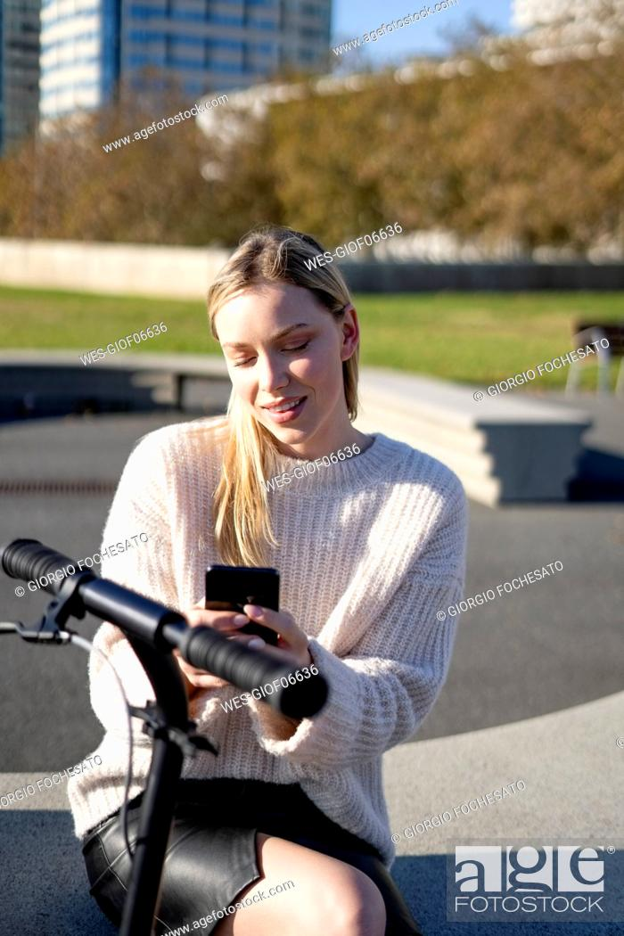 Imagen: Portrait of young woman with kick scooter sitting on bench at sunlight using smartphone.